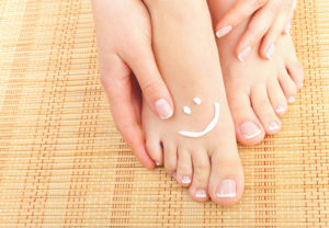 A pair of bare feet with a smiley in cream on them