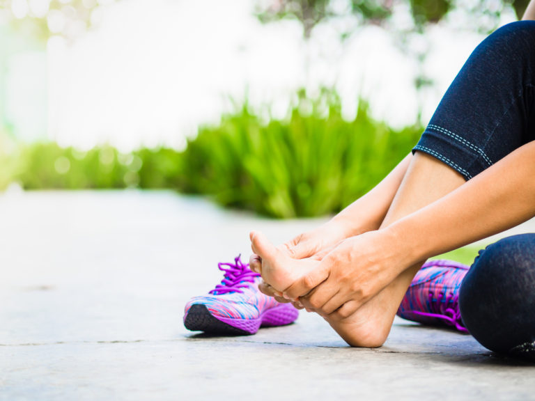 Young woman massaging her painful foot from exercising and running Sport and excercise concept.